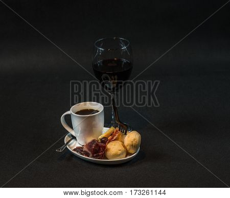 small snack consisting of meat and sausages French cheeses fresh crunchy bread black coffee and red wine tasty snack