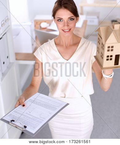Portrait of female architect holding a little house, standing in office