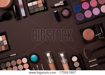 Top view on set of cosmetics for professional make-up on brown background. Still life. Copy space