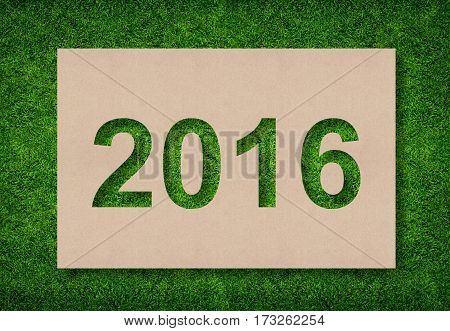 Year 2016 - Alphabet number of brown paper with green grass for background.