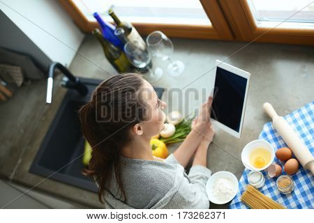 Woman baking at home following recipe on a tablet.