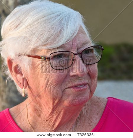 Outdoor Portrait of a Smiling Older Woman wearing Glasses