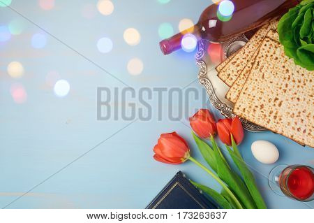 Passover holiday concept seder plate matzoh and tulip flowers on wooden background with bokeh overlay. Top view from above