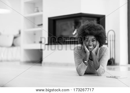 beautiful young black women used tablet computer on the floor of her luxury home in front of fireplace autumn day
