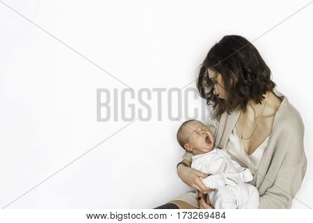 new born baby boy sleeping,  yawing on mother's arm. isolated background