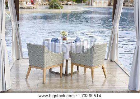 Table with white and blue napkins skateryu for two by the pool. Romantic dinner by the pool.