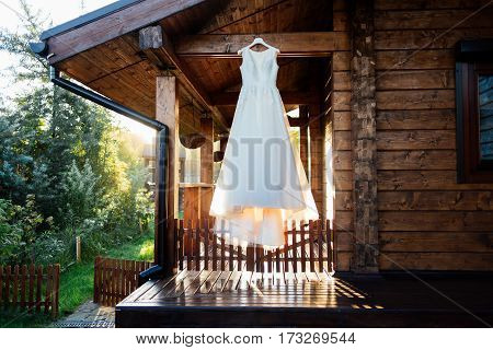 A beautiful cream wedding dress hanging on the wall near the wooden house