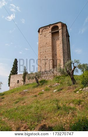 Medieval stone tower on the top of the hill surrounded by olive and cypress trees, Mount Athos, Greece