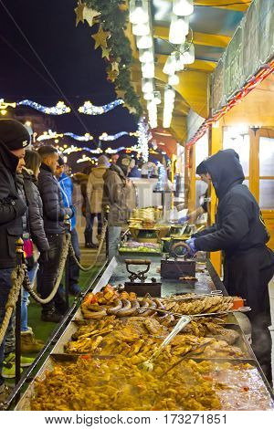 DEBRECEN, HUNGARY - DECEMBER 13, 2016: People taste local food during traditional Christmas Market on Kossuth square (Kossuth ter) in center of Debrecen old town