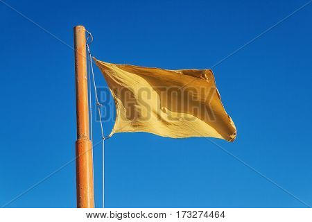 Yellow flag on a background of blue sky.