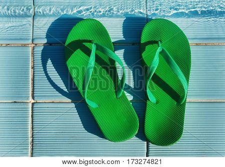 green flip flops standing on the blue tile pool.
