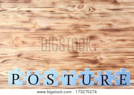 Blue puzzles with word POSTURE on light wooden background