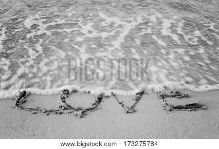 On the sand written word and his love washes wave, black and white.
