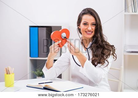 Portrait of beautiful female doctor holding heart shape and stethoscope at her office.
