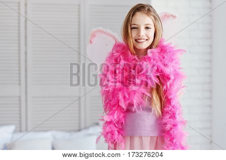 Fairy tale. Positive delighted young female person wearing pink feather shawl looking straight at camera while standing in her bedroom