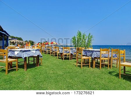 Tables and chairs by the sea in Kos (Greece)
