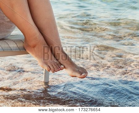 Bare legs girl in a white dress touched the sea water..