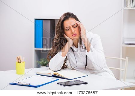 Female doctor is having headache while working at her office.