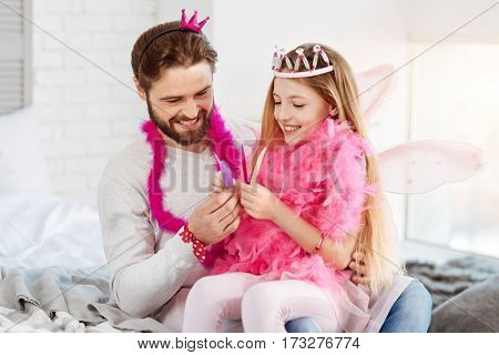 Look at this. Happy princess sitting on the knees of her father wearing pink shawl while showing different feathers to him