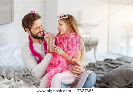 Have fun. Positive delighted bearded man wearing pink accessories keeping his daughter on his hands while playing with feather