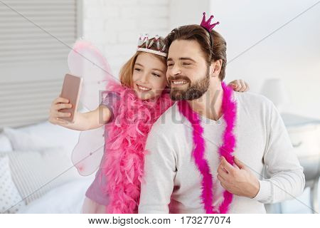 Time for photo. Picture of happy father and daughter wearing pink accessories for masquerade spending time with pleasure while taking photo on phone