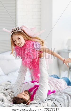 I am princess. Positive delighted girl wearing pink wings and feather shawl stretching her arms while looking on camera