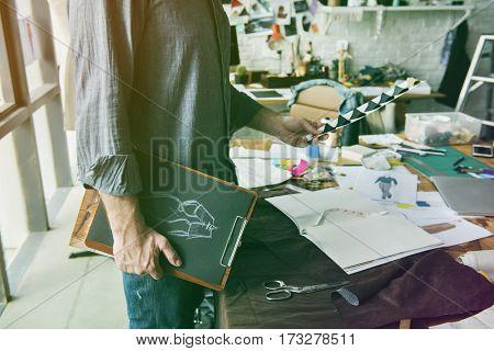 Fashion designer holding clipboard of dress pattern