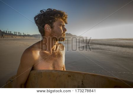 Portrait of a young surfer with surfboard under his arm standing on the beach while inspecting the waves in the early morning sunlight.