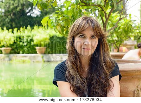 Nice girl with long hair posing in a public square of Tivoli near an artificial lake and a lemon tree