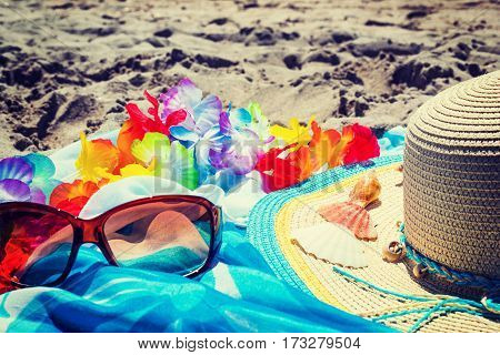 glasses and straw hat on the sand
