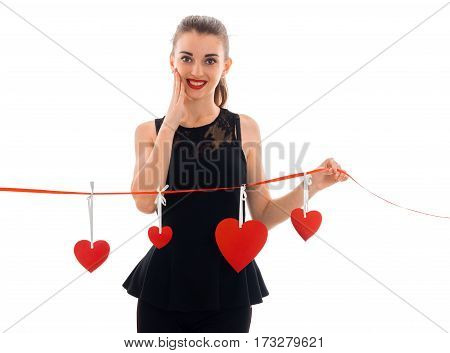 Beautiful young girl in a black dress smiles and holds in her hand a ribbon of red hearts isolated on white background.