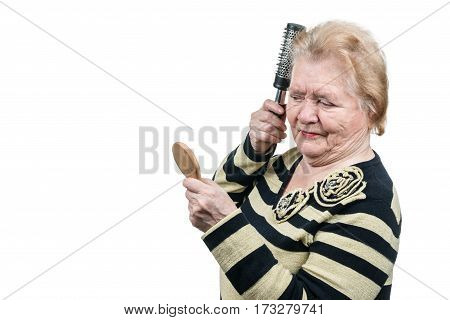 Old woman brushing her hair in front of a small wooden mirror isolated on white background