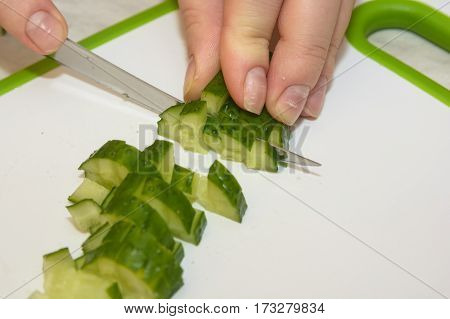 Close up of hands, cutting board and knife slicing cucumber for salad.