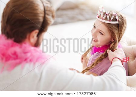 Good time. Attractive longhaired girl holding pink feather around her neck keeping smile on her face while looking on father