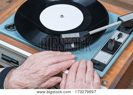 Hands of an old woman lying on an old turntable, close-up