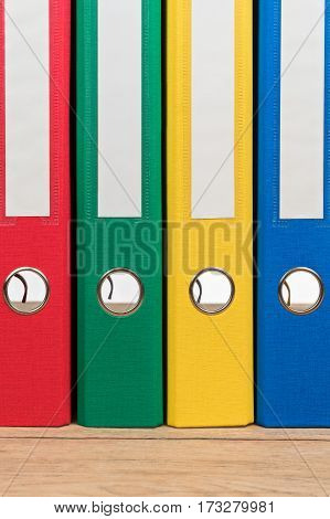 Colored file folders standing next to each other on a wooden table as background