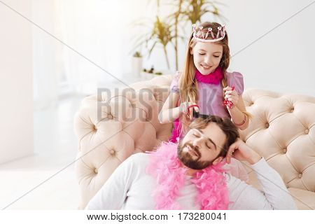 Keep calm. Attractive longhaired girl holding pink feather around her neck keeping smile on her face while brushing hair of her father