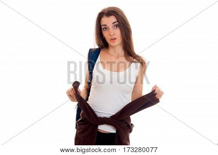 Surprised a young girl in a white t-shirt looks straight and holding in her hands her jacket isolated on white background.