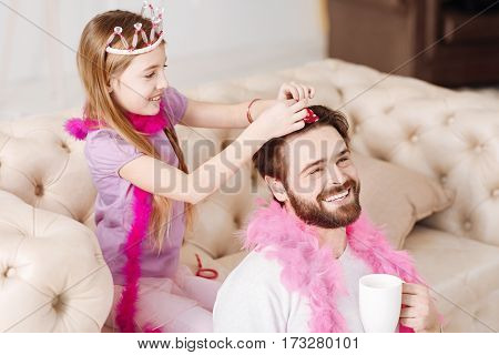 Just relax. Positive delighted girl wearing crown on her head making new hairstyle for her dad while controlling process