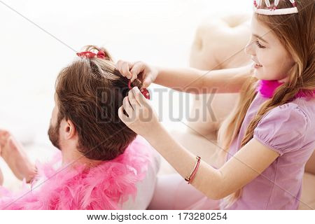 Nice one. Delighted girl wearing crown on her head making new haircut for her father while looking at the process