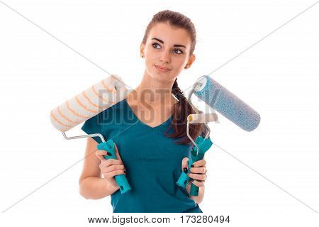 Young girl holds in her hands rollers for painting walls isolated on white background