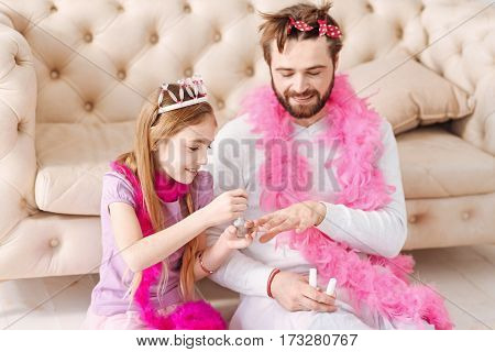 Best color. Positive girl keeping smile on her face holding nail brush in right hand while playing with daddy