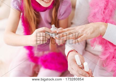 New color. Photo of male hands being under influence of daughter that holding nail polish in left hand while painting nails