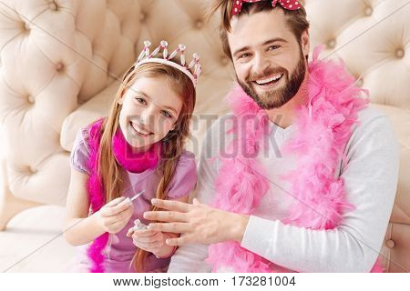 Be in good mood. Smiling girl wearing pink crown on her head holding nail brush in right hand while posing on camera