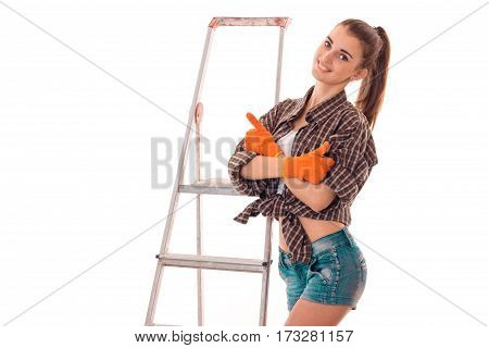 Beautiful young girl with work gloves and shorts standing near the ladder and smiling isolated on white background.