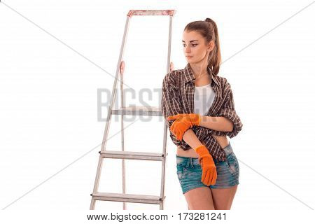 Young attractive girl with work gloves stands near ladder to repair isolated on white background