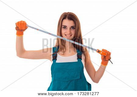 Smiling young girl in overalls holding a measuring tool for DIY repair isolated on white background