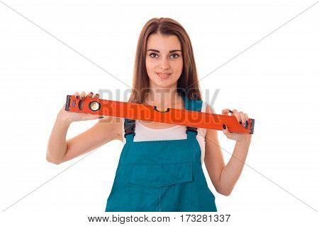 Young girl in overalls holding a level instrument isolated on white background.