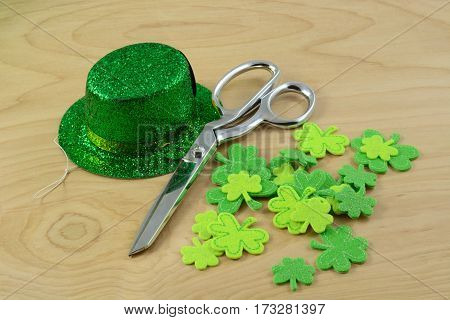 St. Patrick's Day crafting project with green hat and shamrocks and scissors on table