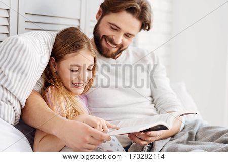 Happy time. Handsome bearded man keeping smile on his face embracing his daughter while holding book